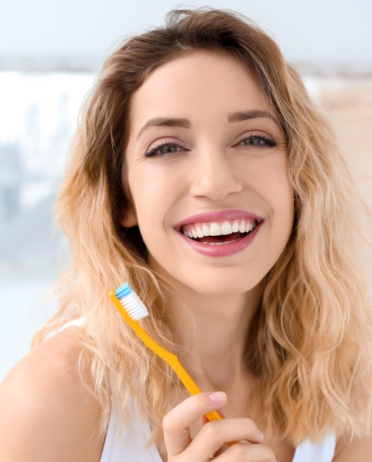 woman smiling with tooth brush 1